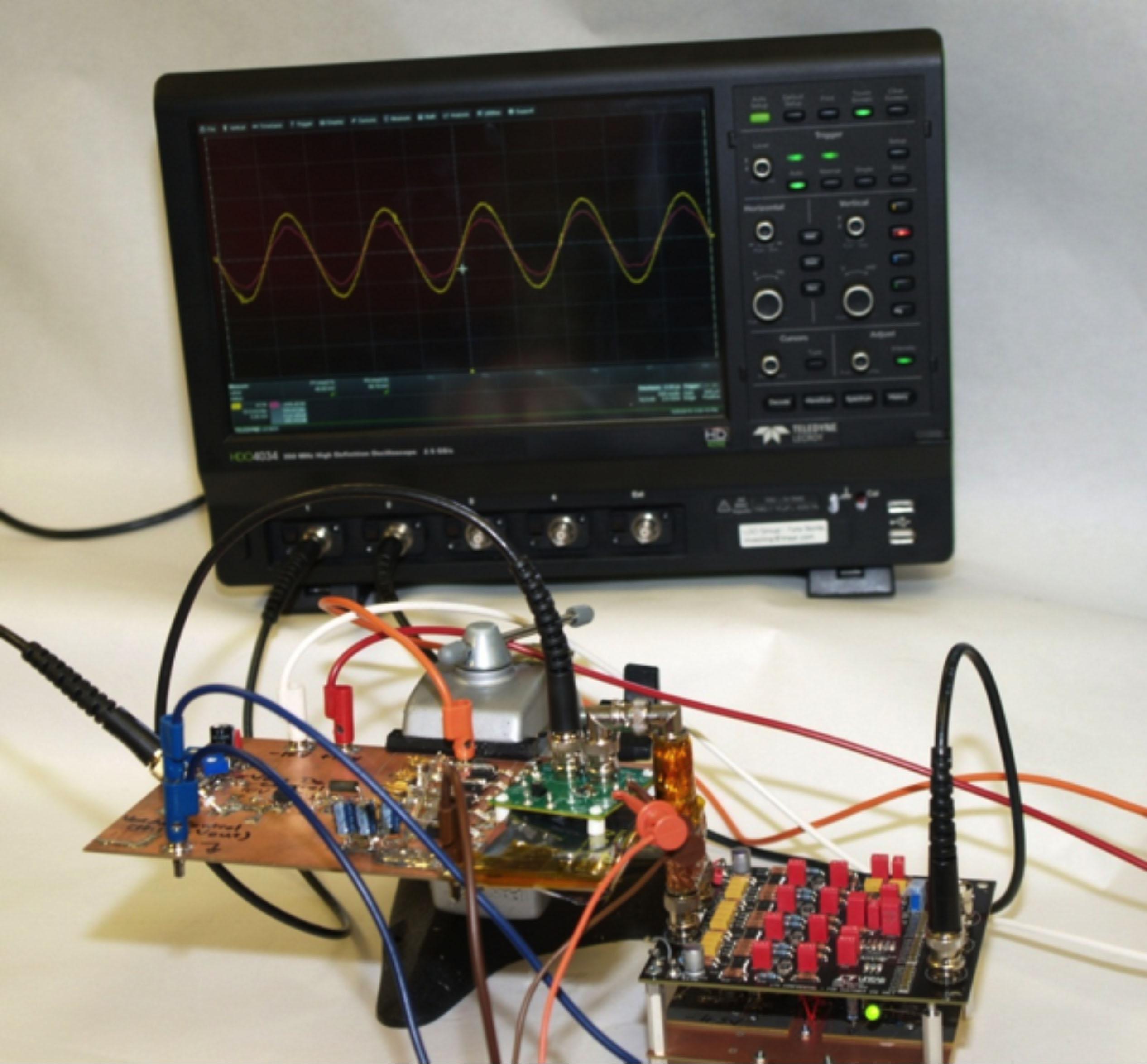 Figura 17. Configurazione per misure di reiezione di segnali dell'alimentatore. Scheda di pilotaggio e dispositivo in prova in basso a sinistra, scheda dell'amplificatore in basso a destra. Alimentatori e generatore di segnale non illustrati.