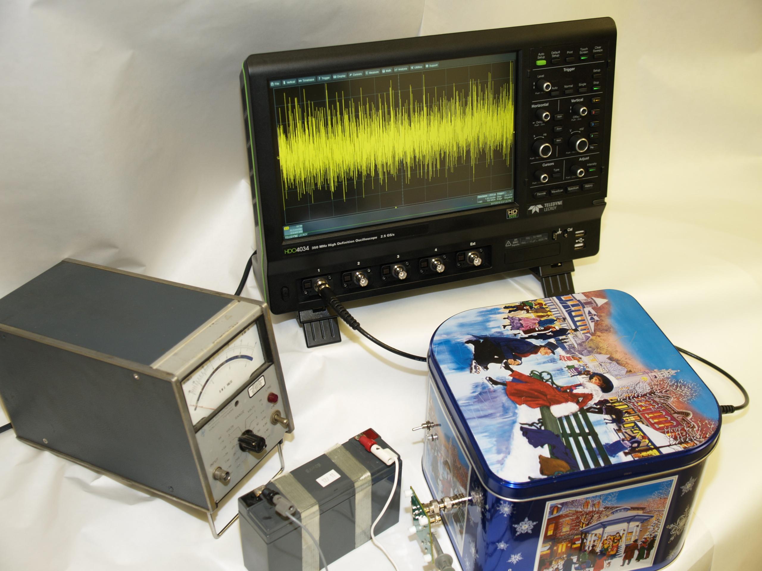 Figura 9. Configurazione del banco di misura del rumore. Il contenitore schermato ospita l'amplificatore di rumore; la bassa impedenza di uscita del regolatore lineare elimina la necessità di schermatura ma i campi magnetici possono ancora influire sull'uscita.